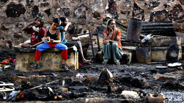 A family sits amid the burnt debris of their hut after a fire br